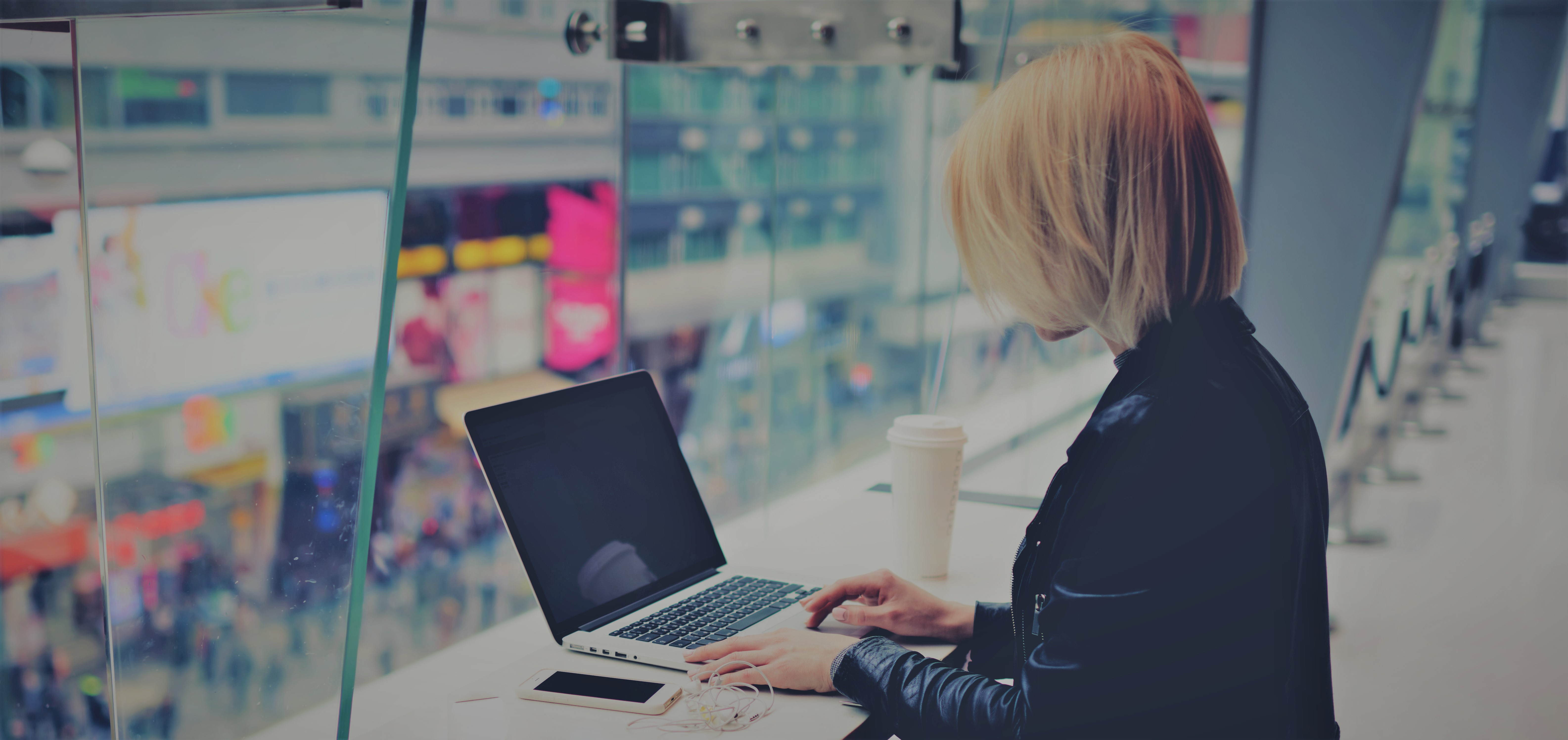 woman on laptop looking out windows